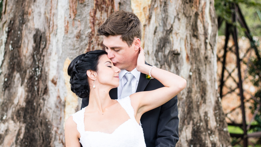 Tim & Pat kissing in front of a tree