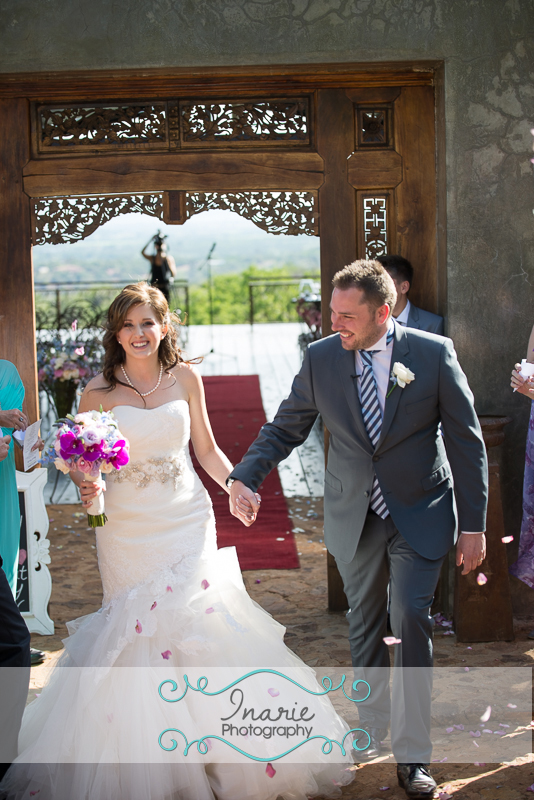 Bride and Groom walking out the chapel, rose petals thrown