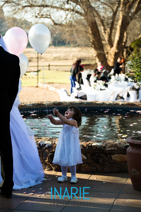Flower girl playing with balloon at wedding