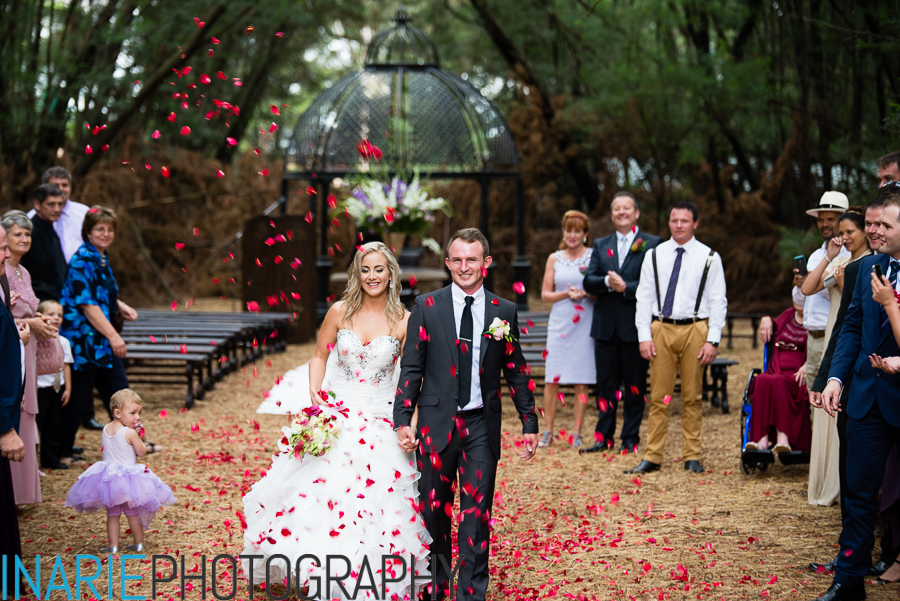 Bride and groom showered with rose petal confetti