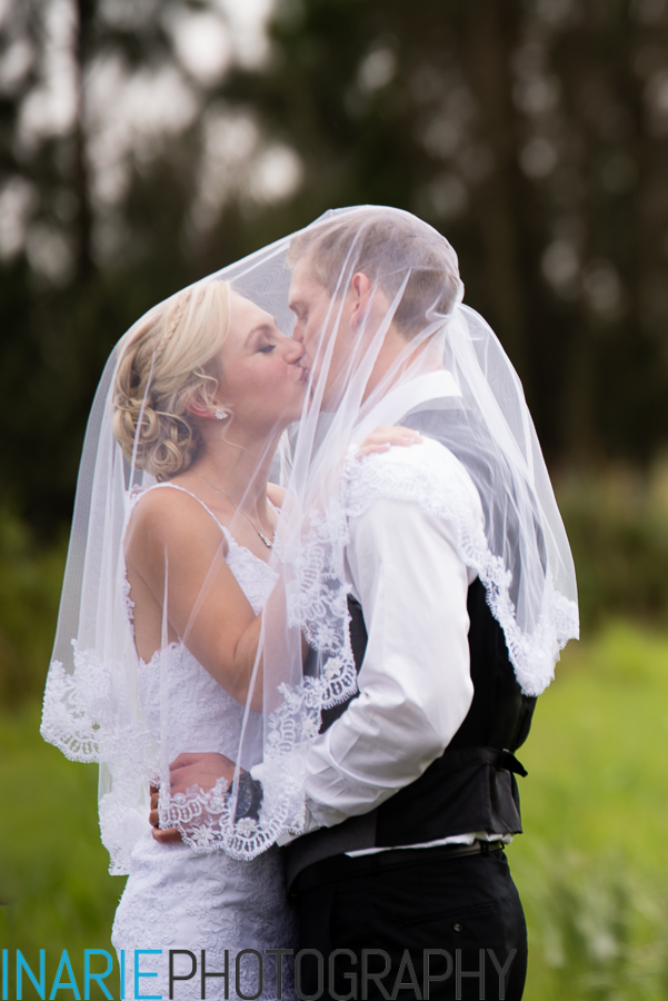 Bride and groom kissing under her veil