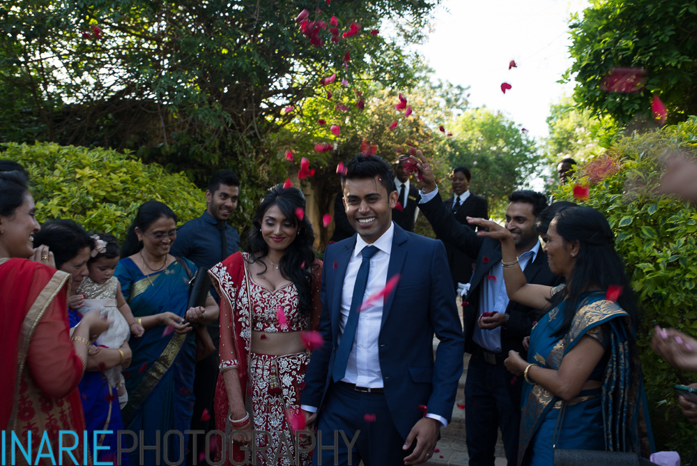 Deepesh and Shinu with guest tossing red rose petal confetti
